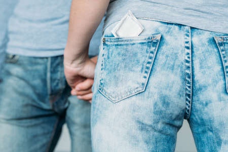 safe love and health concept. condom protection from hiv and aids. backview of a woman with a contraceptive in her jeans pocket