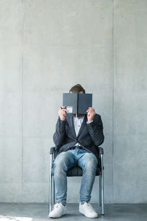 business man covering face with notebook. fear or anxiety before job interview.