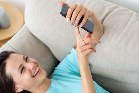 laughing woman laying on the couch using phone. idle lifestyle and mobile devices addiction. 版權商用圖片