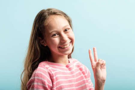 victory sign. piece gesture. smiling adolescent girl portrait on blue background. Reklamní fotografie