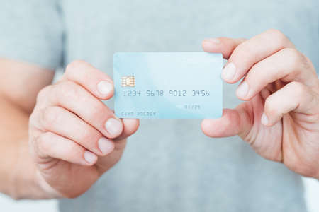 credit card is a key to your banking account. money management and financial operations. man holding plastic card. Stockfoto