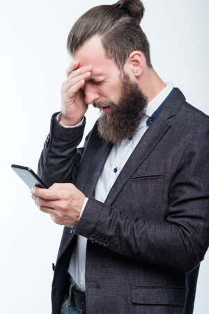 man grasping head and holding phone. failure and emotional reaction to bad news. Stock Photo