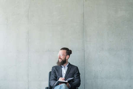 smiling man looking sideways holding day planner . business training seminar