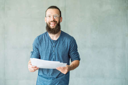 smiling man holding papers. report studying and data analysis. Banco de Imagens