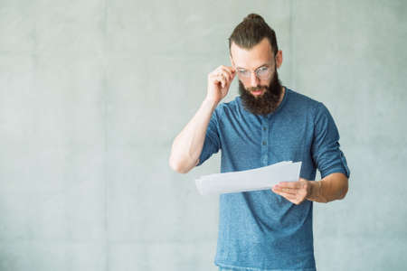 shocked man reading script on papers. amazed impressed screen writer