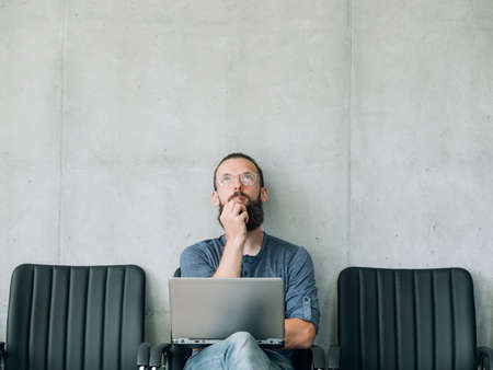 pensive thoughtful man looking up. job candidate and business recruitment concept. empty space for text.