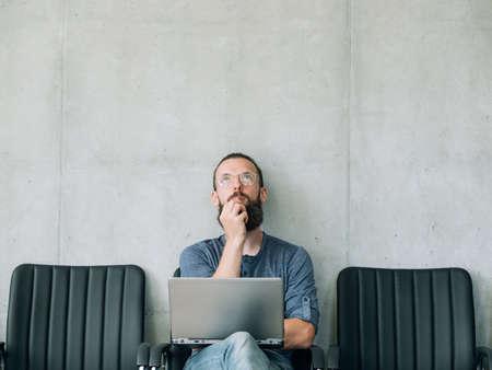 nachdenklicher nachdenklicher Mann, der aufschaut. Bewerber- und Geschäftsrekrutierungskonzept. leerer Platz für Text.