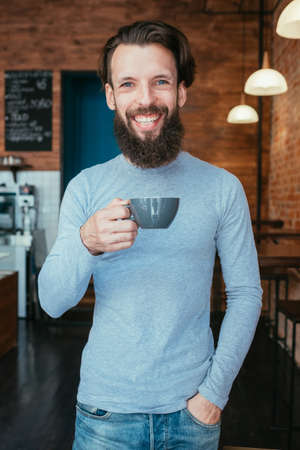 smiling happy man standing in coffee shop holding cup of hot drink. caffeine energy boost