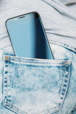 mobility and online internet access through gadgets. phone in woman back jeans pocket Banque d'images - 112738705