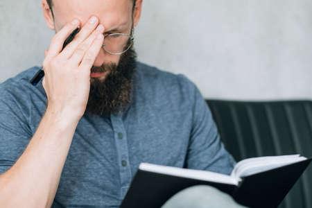 Mann umklammert seinen Kopf beim Arbeiten und Schreiben im Notizbuch. Müdigkeit Kopfschmerzen Müdigkeit und Überarbeitung.
