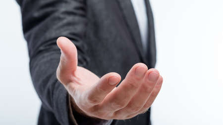 business man holding invisible object in palm of hand. work result virtual projection. product placement