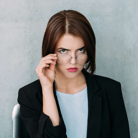 serious grumpy confident business woman looking at camera holding eyeglasses. Stock Photo