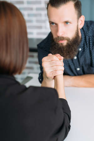 business man and woman arm wrestling at table. power control and office conflict
