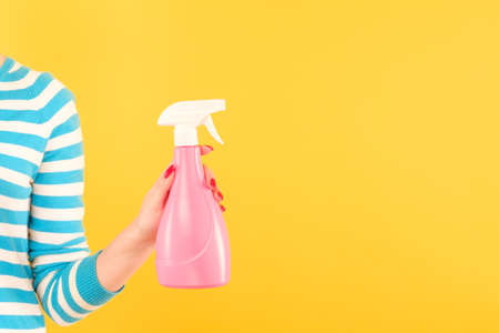woman holding pink spray bottle on yellow background. home cleaning Foto de archivo