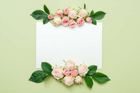 greeting card mockup. empty white paper with roses arrangement on green background