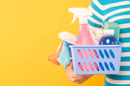 woman holding box of various cleaning products and sponges on yellow background