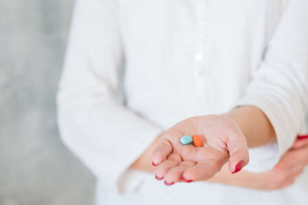 woman outstretching hand with two colorful pills holding hand on belly. pain medication and health problems Banco de Imagens