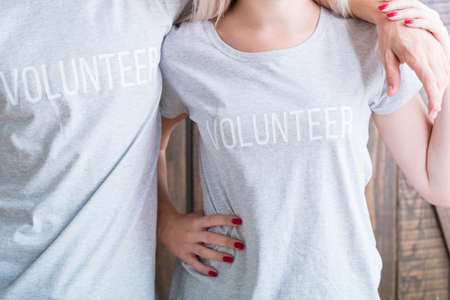 midsection of man and woman wearing casual t-shirts saying Volunteer. social awareness and concern 写真素材