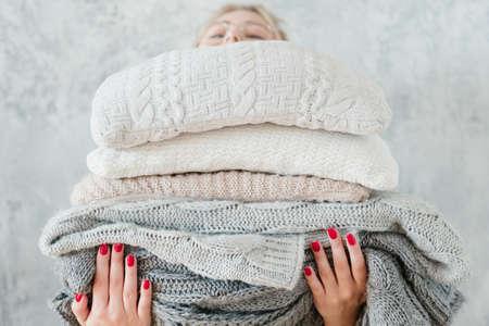 vrouw met grote stapel gebreide plaids en dekens. gezellig en warm winterhuisdecoratie Stockfoto