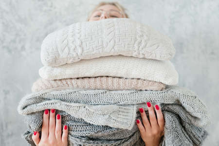 woman holding big stack of knitted plaids and blankets. cozy and warm winter home decor