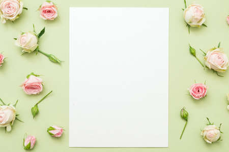Womens day greeting card mockup. Blank paper sheet on green background. Rose border decor. Foto de archivo