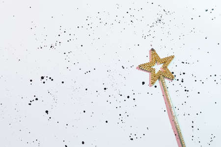 Grant a wish. Star shaped gold magic wand. Copy space on white spotted background.