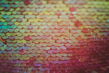 Abstract sequin design. Orange red fabric texture. Defocused background. Stock Photo