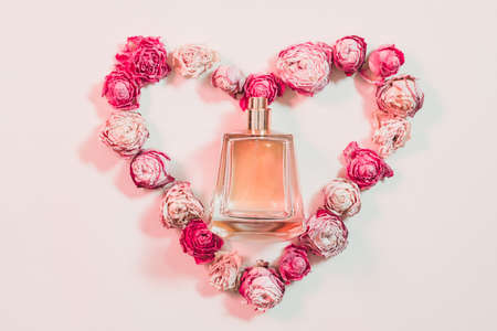 Valentines day gift. Greeting composition. Perfume and heart shaped dried roses on ivory background.