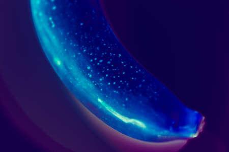 Conceptual art. Vivid glow design. Banana on purple gradient background close up.