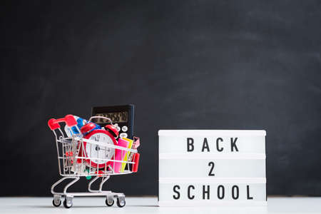 School supplies shopping. Education concept. Lightbox and cart on blackboard background. Stock Photo
