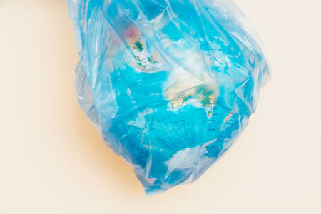 Plastic environmental disaster concept. Globe in captivity of tight bag. Contrast ivory background. Stock Photo - 116051242