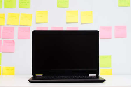 Day planning. Laptop with black screen. Defocused schedule board background.