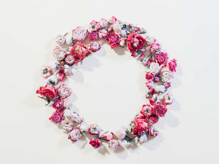 Festive flower composition. Congratulation concept. Dried rose wreath on ivory background.