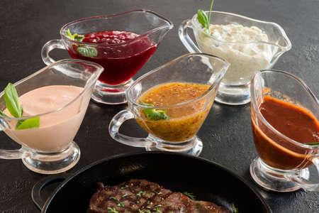Restaurant menu. Roasted meat and sauce assortment on dark grey background.