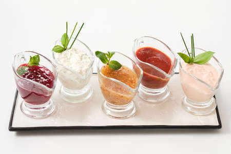 Gourmet cooking concept. Set of assorted sauces. Glass gravy boats on white ceramic platter. Banco de Imagens