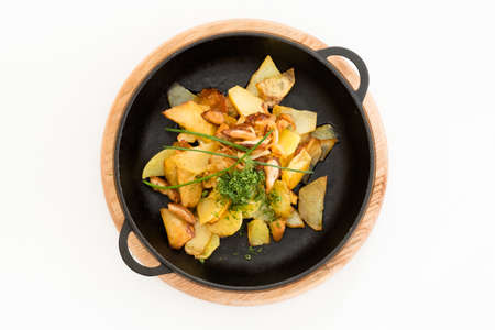 Fried potato garnished with herbs. Full skillet on tray. Flat lay food composition. Reklamní fotografie