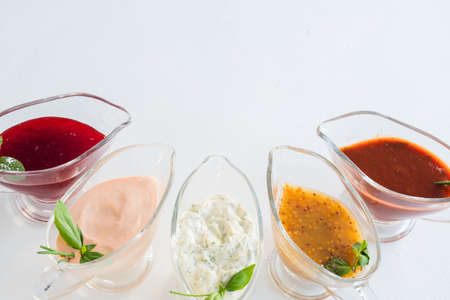 Spicy cooking set. Assorted sauces in glass gravy boats. Copy space on white background. Stock Photo