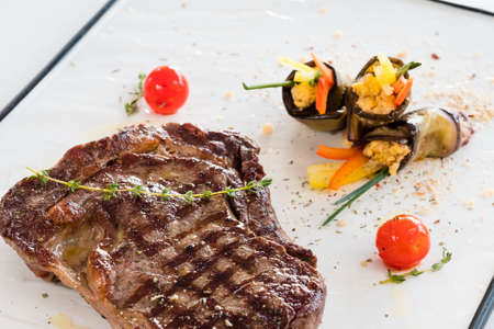 Restaurant meal background. Grilled beefsteak main course garnished with vegetables. Stock Photo