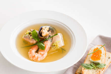 Restaurant cooking. Seafood soup plate and cheese caviar sandwich on white background.
