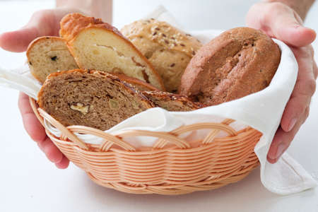 Bakery business. Startup concept. Wicker basket with bread assortment in hands.