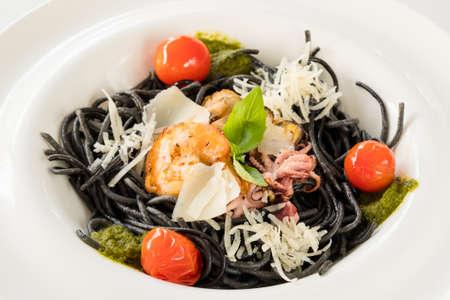 Fine cuisine food composition. Fresh black tagliolini pasta with chicken and tomato.