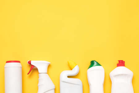 Housekeeping concept. Cleaning services chemicals. Row of plastic detergent bottles. Copy space on yellow background.