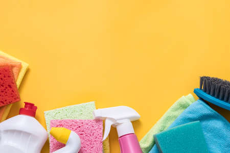 Disinfection concept. Cleaning supplies variety. Copy space on yellow background.