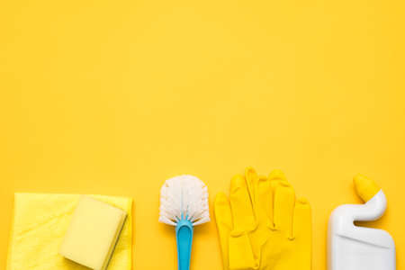 Toilet cleaning supplies. Basic cleanup set flat lay. Copy space on yellow background. Stock Photo