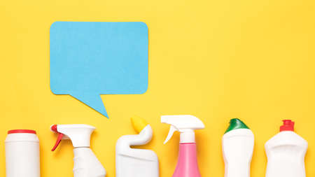 Housekeeping services review. Row of cleaning supplies and detergents . Blue speech bubble on yellow copy space. Stock Photo