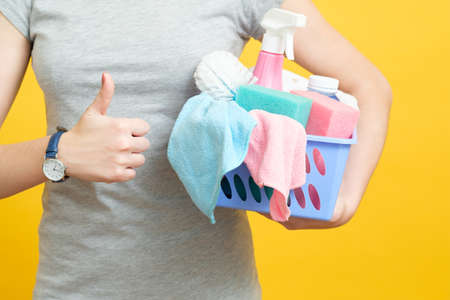 Quality housekeeping. Housewife thumb up. Woman with basket of cleaning supplies on yellow background.