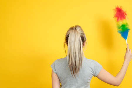 Early spring regular cleanup. Woman with feather duster backview. Copy space on yellow background. Stock Photo