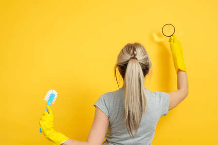 Cleaning company. Professional home office cleanup. Woman in rubber gloves with magnifier and brush on yellow background.