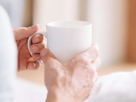 Wake up beverage. Man hands with white cup of hot morning drink. Close up.