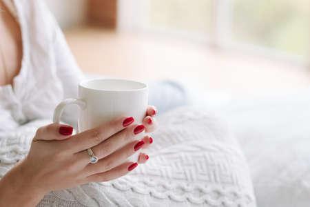 Boisson réconfortante préférée. Rituel du matin. Mains de femme avec une tasse de boisson chaude.